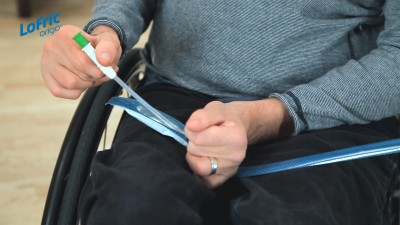 Wellspect Lofric Photo of man in wheelchair opening Origo catheter packaging